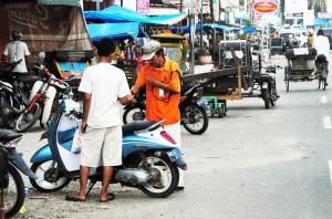 Petugas parkir kenderaan roda dua sedang melakukan pengutipan uang retribusi parkir di pusat pasar lama kota Panyabungan ibukota Kabupaten Mandailing Natal.